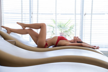 beautiful slender girl in bikini relaxes on spa treatments at the resort