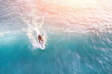 Surfer in the ocean in the sunlight, top view