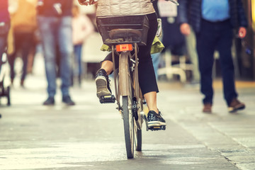 A woman is riding a bike on a city street on a sunny day