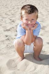 fun little boy sit on sand beach during vacation day summer