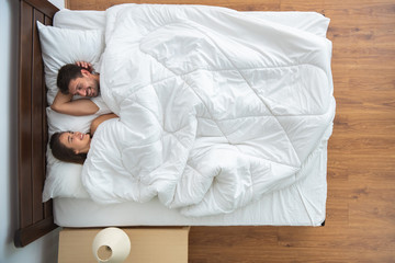 The couple laying on the bed. view from above
