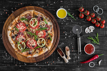 Vegetables, mushrooms and tomatoes pizza on a black wooden background. It can be used as a background