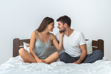 The happy man and a woman sitting on the bed on the white background