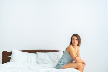 The unhappy woman sitting on the bed on the white background