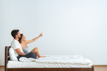 The happy couple on the bed gesturing on the white background