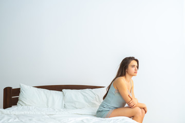 The woman sitting on the bed on the white background