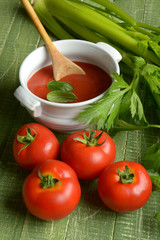 tomato sauce with celery on green wooden table