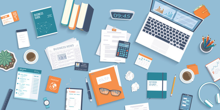 Workplace Desktop background. Top view of table, laptop, folder, documents, notepad, business card, purse, calendar, clock, books,coffee, passport, crumpled paper. Business background, organization.