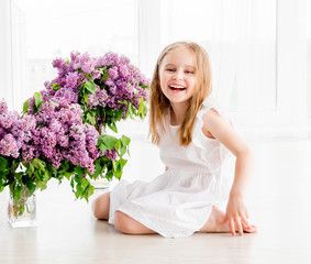 Cheerful little girl in white dress with lilac flowers