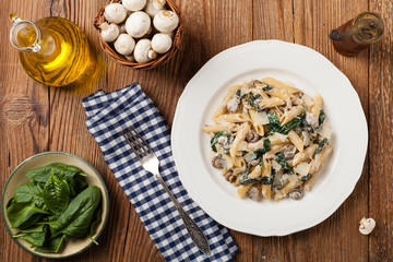 Penne pasta with spinach and mushrooms. Sprinkled with cheese.