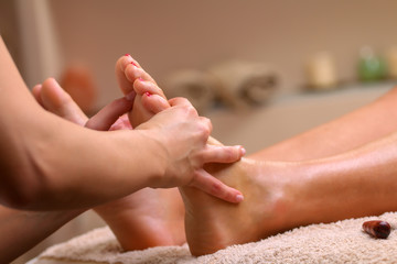 Massage therapist massaging legs of pregnant woman