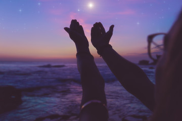 Silhouette of a girl with praying arms in dusk / dawn and glittering stars above the ocean.