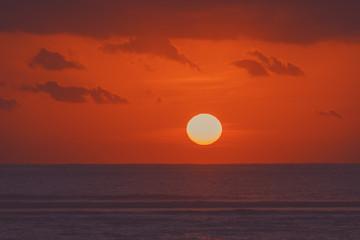 Sunrise over ocean horizon photographed with big telephoto lens.
