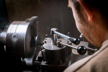 Metal worker working on lathe