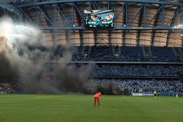 Player stands as spectators throw flares during Polish Championship match between Legia Warszawa and Lech Poznan in Poznan