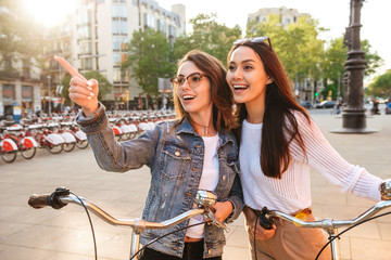 Two young beautiful women friends on the street pointing.