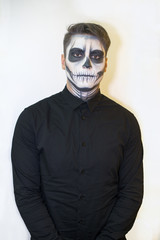 man in make-up Halloween. drawing a vampire, skeleton on his face. Close-up photo.