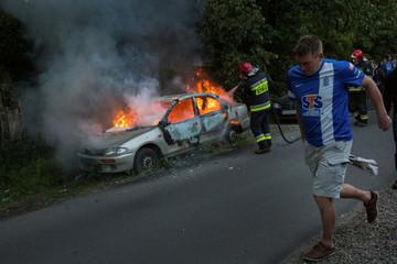 Soccer fan passes burning car after Polish Championship match between Legia Warszawa and Lech Poznan in Poznan