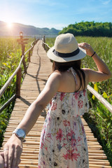 Young Woman traveling in dress with hat, Asian traveler standing and looking forward at jungle or green forest. Summer travel concept