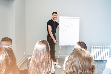 Young businessman presenting important data on a flipchart with smile.