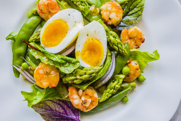 Salad with shrimps and green asparagus with peas.