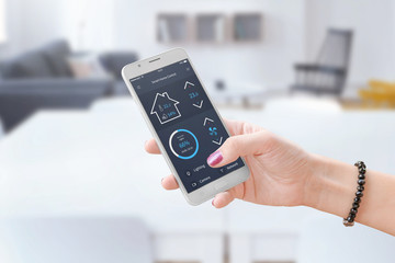 Woman hold smart phone and use smart home control app to monitoring home parameters. Fotoväggar