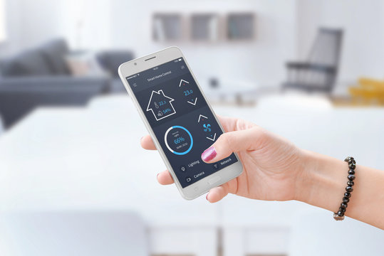 Woman hold smart phone and use smart home control app to monitoring home parameters.