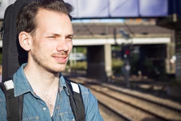 A squinting young man waiting for train on platform, running out of patience, in London
