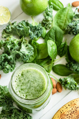 Green Detox Smoothie or Juice in bottle jar. Fresh summer detox drink with kale, broccoli, apple, spinach and lime. Top view