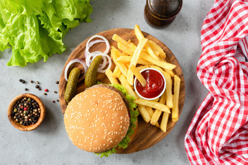 Burger with sesame, fries, pickles and lettuce salad. Top view of homemade beef burger with fries and pickles. Horizontal