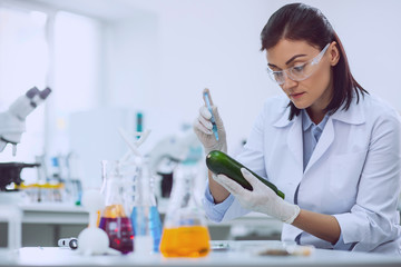 Good quality. Serious female biologist wearing a uniform and testing a marrow squash