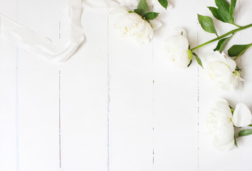 Styled stock photo. Feminine wedding table composition with white peonies flowers and silk ribbon on old white wooden background. Empty space. Top view. Picture for blog.