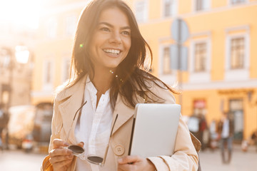 Happy brunette woman in jacket holding laptop computer Wall mural