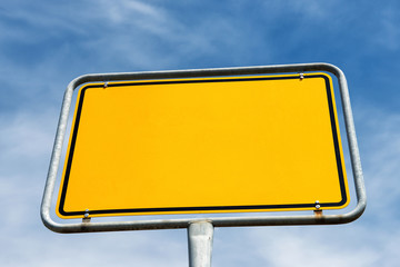 Blank yellow city sign in Germany. Template with copy space isolated on blue sky and clouds