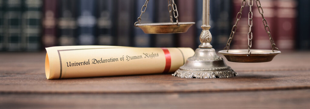 Scales of Justice, Universal declaration of human rights on a wooden background, human rights concept.