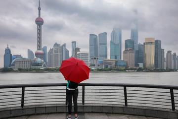 Frau mit rotem Regenschirm steht vor der Skyline von Shanghai an einem verregnetem Tag, China