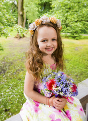 The little happy girl with a bouquet of flowers and in a wreath from roses