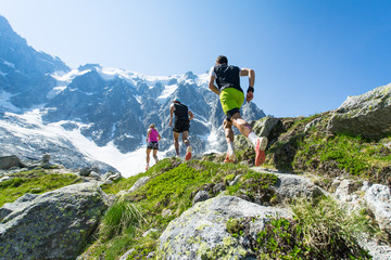 Trail runners running up a steep trail in the Alps in summer
