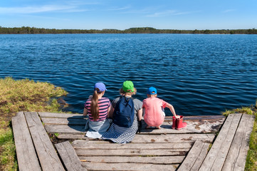 Family sitting on the bank of the forest lake