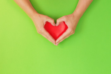 Female hands in shape of heart. With red heart inside on green background. Healthcare and chirty concept.