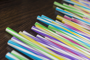 Colorful paper straws on a wooden background. Accessories for events and parties.