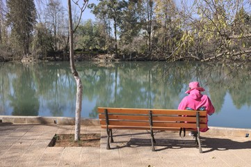 Isolated woman on the bench dressed in fuchsia (Lijiang, Yunnan, China)