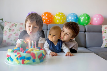 Cute children, boy brothers, celebrating birthday with colorful cake, candles, balloons