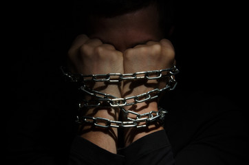 A man prisoner chained in a chain clinging to his head against a black background