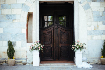 gate of a Romanesque church with flower vases on the sides, decorations for a wedding ceremony
