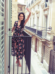 Beautiful young woman standing on balcony in city
