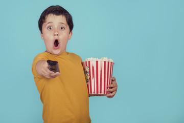 niño sorprendido con palomitas de maíz y mando a distancia de televisión sobre fondo azul