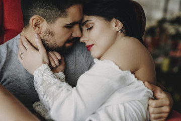Close up portrait of a beautiful couple sitting face to face while man is holding her love on his arms with closed eyes smiling in a red chair.