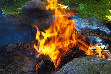 bonfire between boulders against the background of green grass