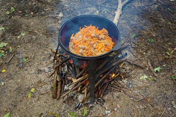 meat with carrot in a cauldron over a fire